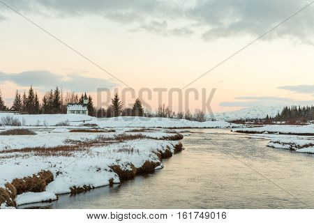The Thingvellir church in a lagoon of melting snow and streams converging in the river towars lake Thingvallavatn in Iceland. Landscape in low evening light with orange colored sky