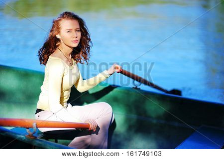 amazing beautiful haired girl swims on a wooden boat and rowing with oars