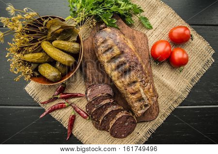 Homemade blood sausage with offal on a black wooden background