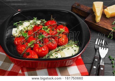 Roasted (baked) cherry tomatoes with mozzarella cheese in red ceramic baking dish of tomatoes. Ingredients for baked (Roasted) tomatoes parmesan cheese thyme lettuce. Dark black wooden background.