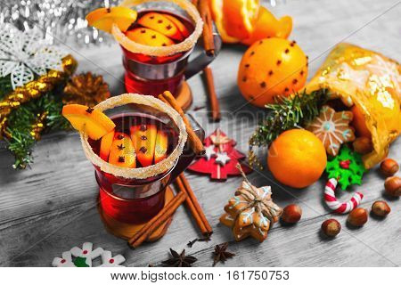 Winter Christmas drink hot mulled wine. Ingredients for mulled wine oranges cinnamon anise. Glasses with mulled wine decorated with sugar. Christmas gift with sweets nuts. White wooden background.