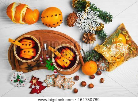 Winter Christmas drink hot mulled wine. Ingredients for mulled wine oranges cinnamon anise. Glasses with mulled wine decorated with sugar. Christmas gift with sweets nuts. White wooden background. Top view