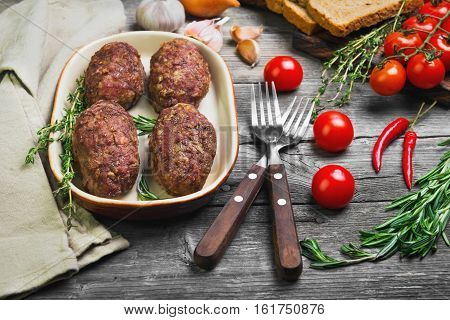 Meat cutlets on ceramic dish. Ingredients for meat chops garlic cherry tomatoes onions rosemary thyme bread pepper. Special forks for cutlets on Gray wooden background cloth.