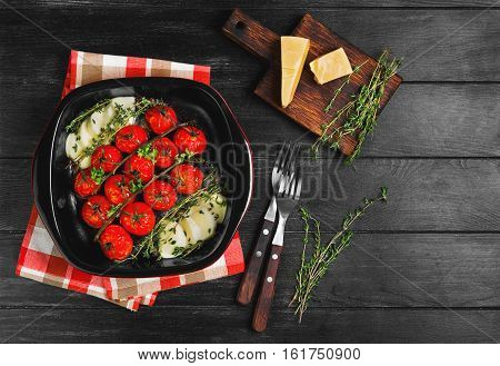 Roasted (baked) cherry tomatoes with mozzarella cheese in red ceramic baking dish of tomatoes. Ingredients for baked (Roasted) tomatoes parmesan cheese thyme lettuce. Dark black wooden background. Top view