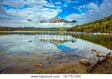 Mount Pyramid beautifully reflected in the water. Pyramid Lake in the Canadian Rockies. The concept of leisure and tourism