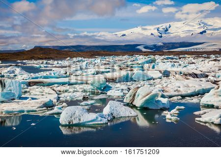 The concept of extreme northern tourism.  Northern nature. Drift ice Ice Lagoon - Jokulsarlon. White-blue ice is piled up in turquoise water of the lagoon