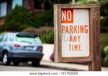 No Parking Anytime - Sign made of wood with car on the background