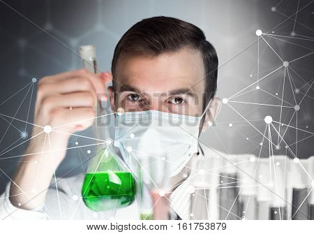 Young scientist mixing reagents in glass flask in clinical laboratory