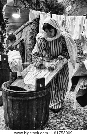 Riva del Garda Italy - December 26 2015: Laundress washes clothes with soap and water on a wooden board.