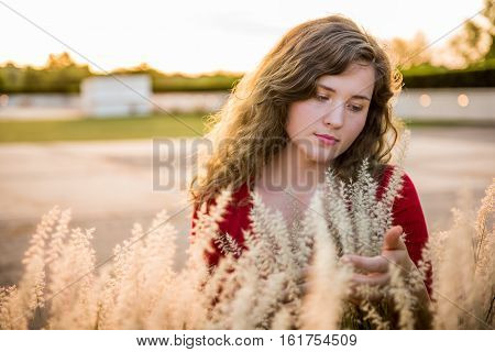 Portrait of young woman holding dry wheat grain grass illuminated in sunlight
