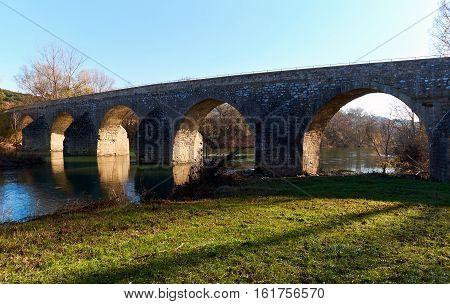 Ancient bridge across Ceze river in La Roque-sur-Ceze. Picturesque village on a southern France. Languedoc-Roussillon