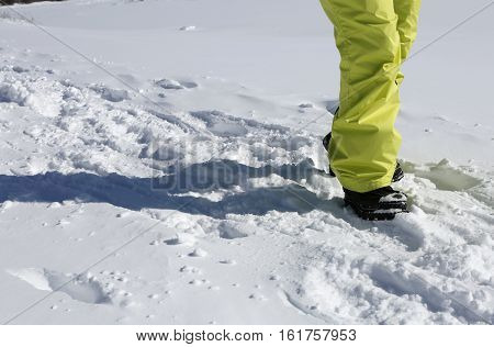 Woman walking a snow path on bright sunny day