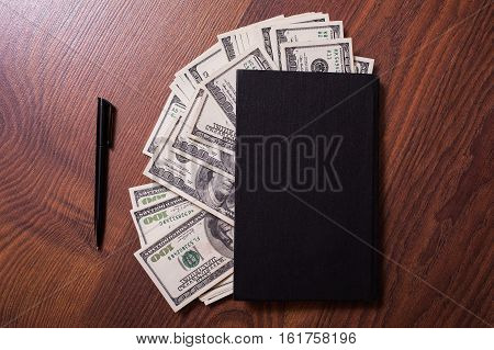 black book pen and money. business plan money background hundred dollar bills front side. background of dollars money in the black book the work of a writer