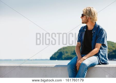 Vacation contemplation concept. Nostalgic man sitting relaxing and enjoying weather during summertime outdoor shot on sunny day