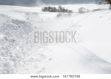 A rural road is closed with blowing drifting snow in Pennsylvania USA.