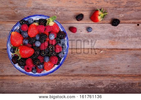 Mixed ripe sweet berries in a blue and white bowl with some berries that have spilt out of the bowl on a wooden background. Blueberries raspberries strawberries and blackberries. With space for text.