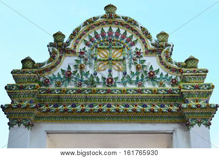 Vintage arch gable of Thai church temple decorate with colorful ceramic tiles