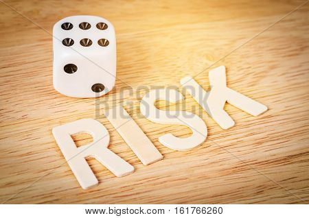 Dice and risk word wooden on wooden background RISK conceopt.