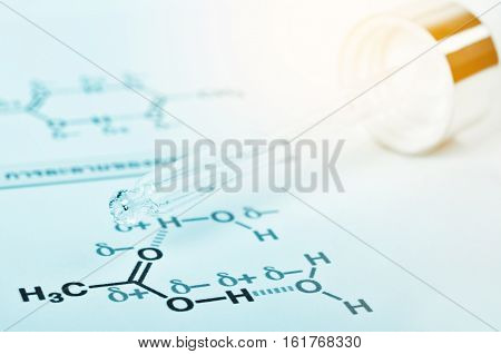 Laboratory glass Pipette on Chemical formula paper with light tone select focus.
