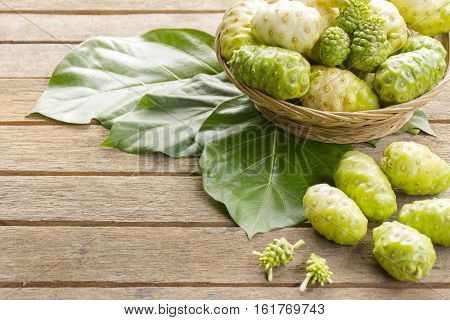 Noni fruit  and noni in the basket on wooden table.Zoom in