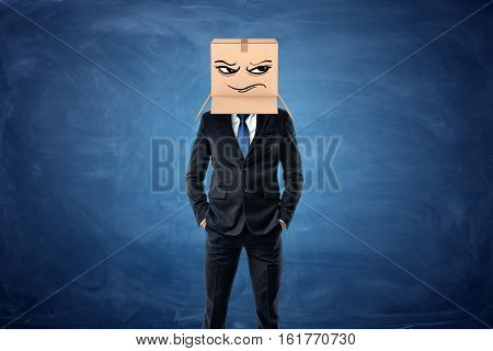 Businessman wearing a cardboard box with a drawn frowning face on his head near the blue chalkboard background. Anonymous person. Packing and crating. Issues of small business.