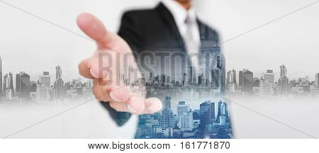 Businessman stretch out hand, with double exposure city and real estate site construction, and hologram futuristic city