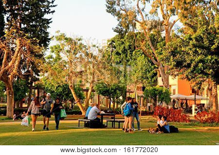 TEL AVIV, ISRAEL- APRIL 7, 2016: Local people are resting on green lawn in the Sarona park, Tel Aviv, Israel. Sarona was a German Templer colony in Tel Aviv which is now a neighborhood of the city.