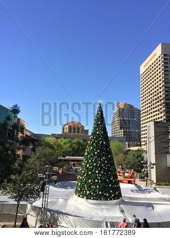 PHOENIX AZ - NOVEMBER 17 2016: White Christmas spirit created by protective highly reflective silver-white tarp covering downtown skating ring with decorated Christmas tree in sunny Phoenix Arizona