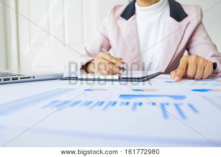 Portrait of business woman with laptop finance graph and writes on a document at her office.