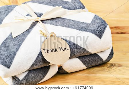 Blanket with Thank you tag gift with ribbon on wooden background. Gift Concept.