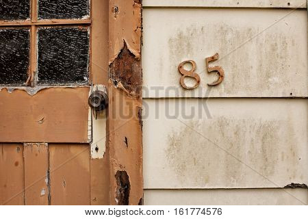 Queenstown, Australia-February 9, 2013. Close up detail of house number on old abandoned house in Queenstown, Tasmania