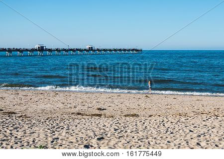 NORFOLK, VIRGINIA - MAY 2, 2015: Young girl playing at Ocean View Beach, with fishermen on the fishing pier in the background on Chesapeake Bay.