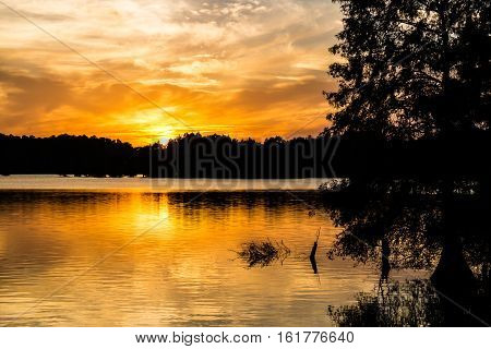 Brilliant orange sun at dusk at Stumpy Lake in Virginia Beach, Virginia.