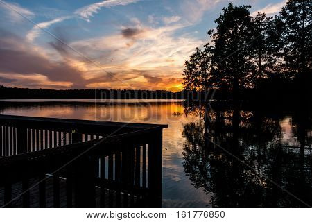 Fishing pier at Stumpy Lake in Virginia Beach, Virginia at dusk.