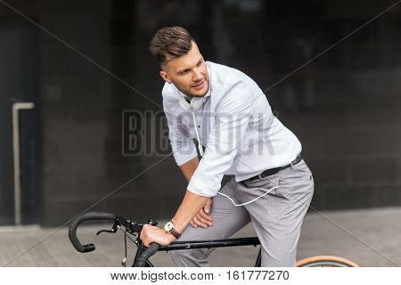 lifestyle, transport and people concept - young man with bicycle and headphones on city street