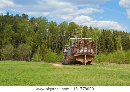Ancient sailing ship on the edge of the forest. Landscape