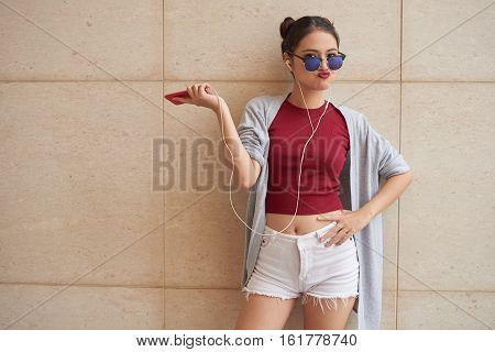 Portrait of arrogant Asian girl with sunglasses and smartphone