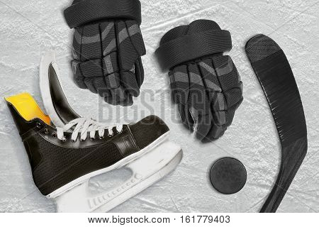 Hockey stick gloves and puck on the ice arena. Concept