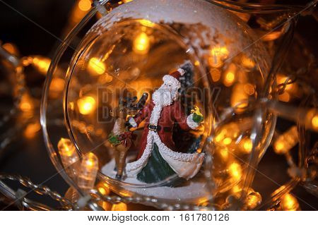 Closeup Photo Of Christmas Glass Toy With Santa Claus And Dear Inside. Yellow Garland Background.