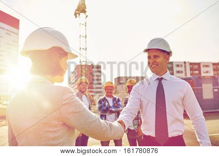 business, building, teamwork, gesture and people concept - group of smiling builders or architects in hardhats greeting each other by handshake on construction site