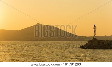Naoussa in Paros island in Greece with a lighthouse during sunset.