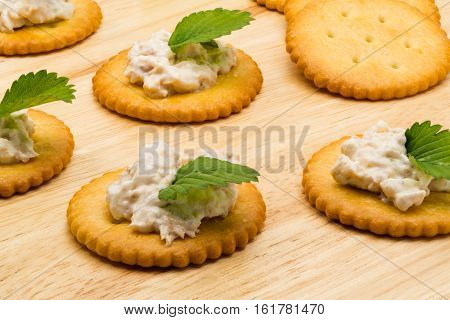 Biscuit crackers with tuna salad on wooden board