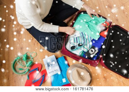 winter holidays, vacation, tourism and objects concept - close up of woman packing travel bag with summer clothes, camera and city guide over snow