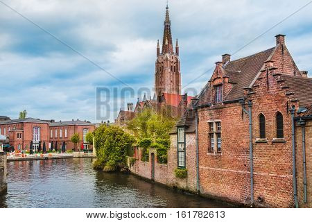 Houses along beautiful canals in spring in Bruges; Belgium. In the background there is the church tower of the famous Onze-Lieve-Vrouwekerk