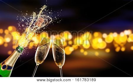 Splashing bottle of champagne with glass over blur colored spot background. Celebration concept, free space for text