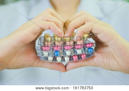 Colorful Medicine Capsule Pill In Heart Shape Hand Of Female Pharmacist.