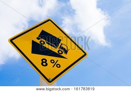 Traffic Sign. Down Hill Sign Warning On Blue Sky And White Cloud Background.
