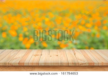 Wood table top on blurred background of yellow flowers.