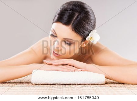 Beautiful, young and healthy woman in spa salon. Massage treatment over grey background. Spa, health and healing concept.