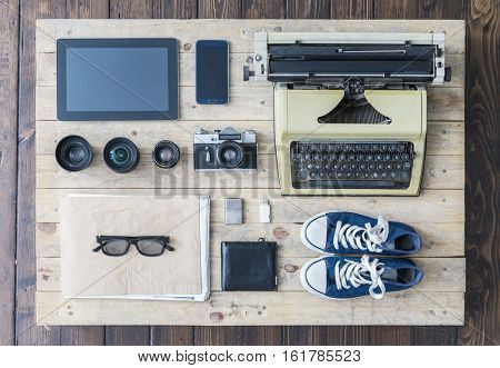 Outfit of a stylish traveler or a freelance journalist. Set of different objects and equipment: tablet, phone, album, glasses, camera, lenses, wallet, gumshoes, usb storage and typing machine.